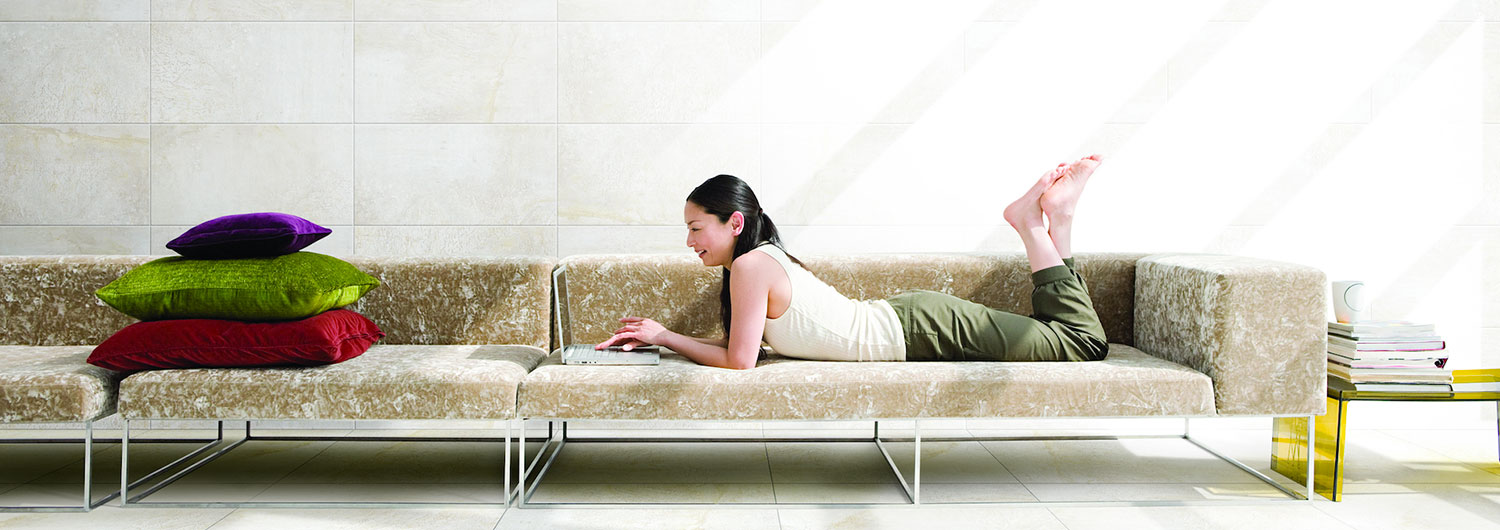Lady lying on couch with cream wall tiles